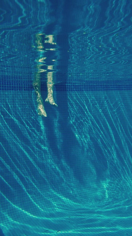 Feet kicking underwater in slow motion