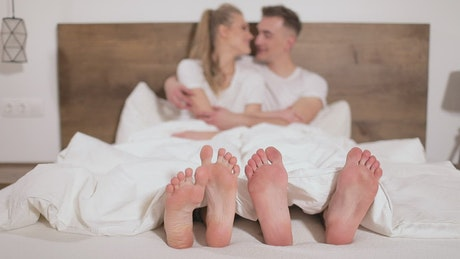 Feet of a couple hugging in bed