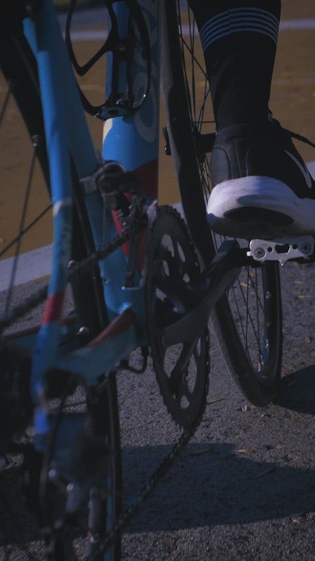 Feet of a cyclist pedaling on a track