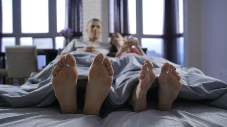 Feet of a man and a woman lying on a bed