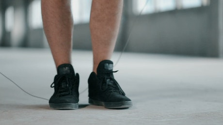 Feet of a man jumping rope