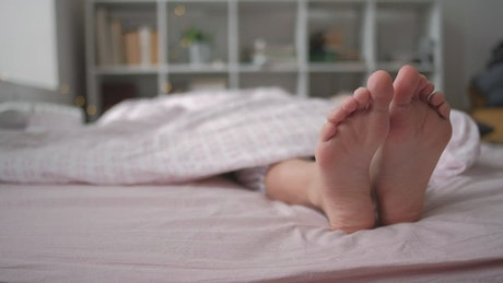 Feet of a person resting on a bed