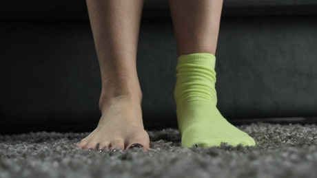 Feet of a woman putting on different colored socks