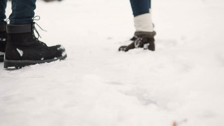 Feet of people running in the snow, tracking shot