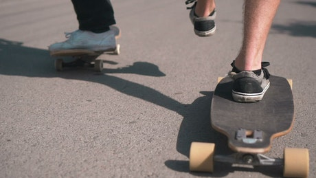 Feet of skateboarders on the street, tracking shot