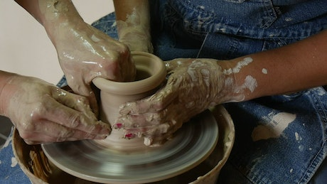 Female and male hands working together on raw clay
