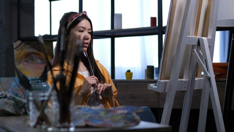 Female artist looking at her work