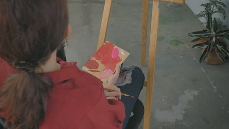 Female artist painting a picture in a workshop