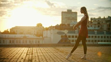 Female ballet dancer taking a leap at sunset