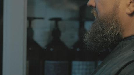 Female barber trimming a long beard