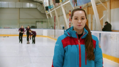 Female curling player head-on on an ice rink
