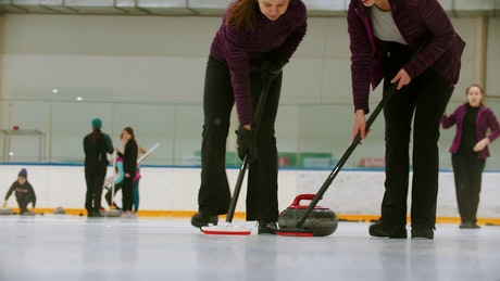 Female curling players in a shot close to the ice