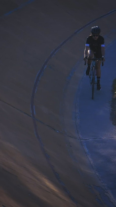 Female cyclist riding down a cycling track by the edge