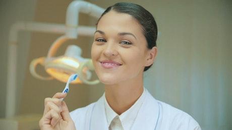 Female dentist teaching how to brush teeth