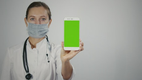 Female doctor displaying mobile with green screen