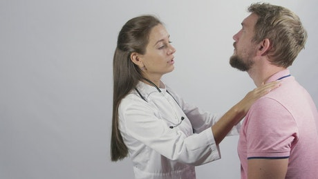 Female doctor inspecting a young man