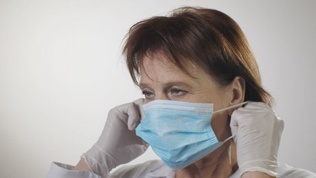 Female doctor puts on a mask, portrait