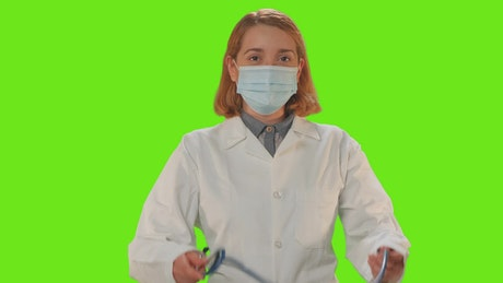 Female doctor with mask on a green background