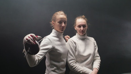 Female fencers head on with a dark background