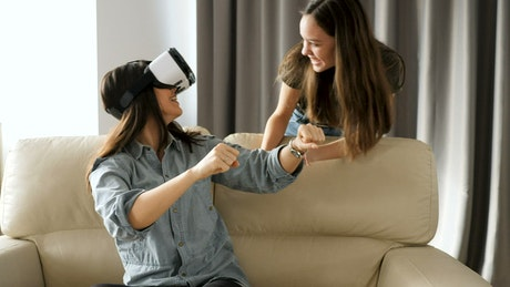 Female friends playing virtual reality video games