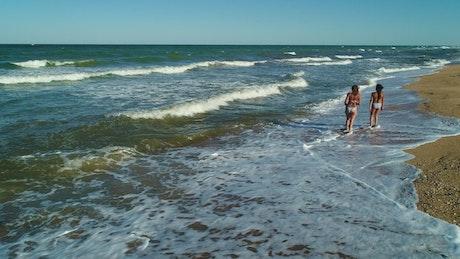 Female friends strolling on the seashore