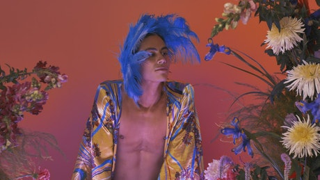 Female gay man surrounded by many flowers