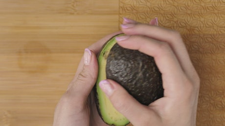 Female hands cutting an avocado in the kitchen