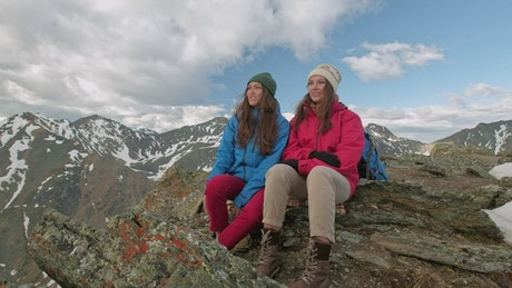 Female hikers sitting on a mountain looking around