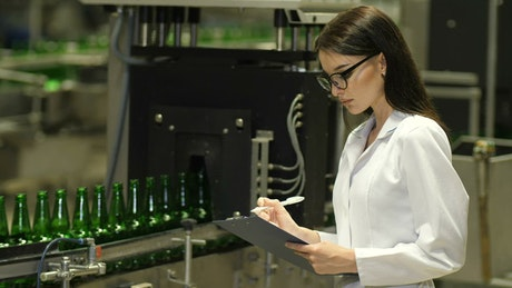 Female inspector checking beer production