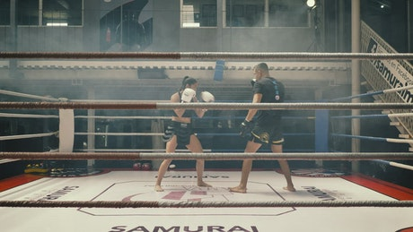 Female kickboxer training with her coach