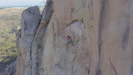Female mountaineer climbing on top of a mountain