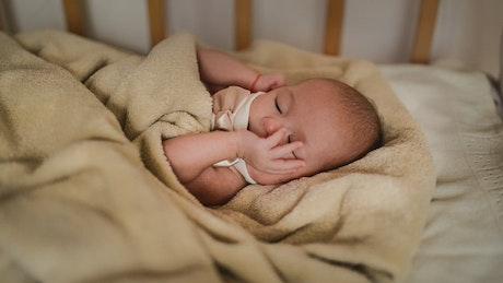 Female newborn baby falling asleep