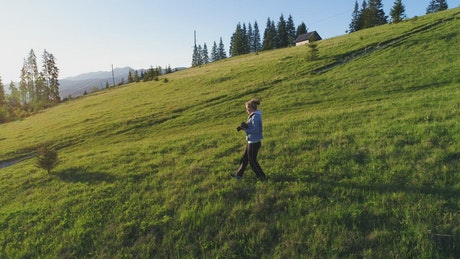 Female photographer walking down a hill and taking photos