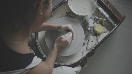 Female potter works on pottery wheel
