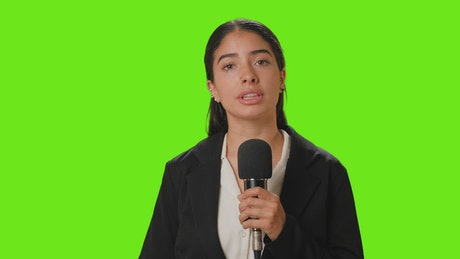Female reporter reporting with microphone in hand on a chroma green background