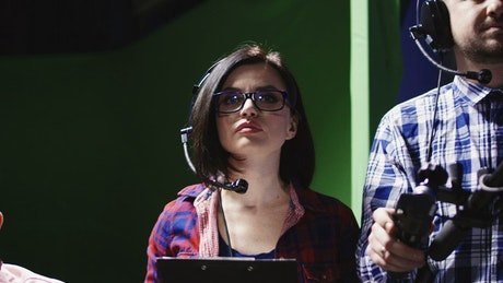 Female stage manager given instructions to crew