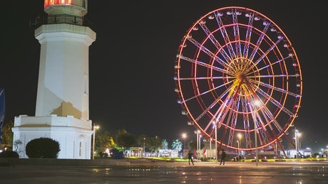 Ferris wheel near the lighthouse at night