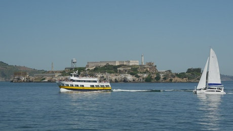 Ferry and Sailboat passing by Alcatraz Island in San francisco