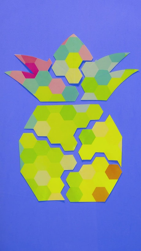 Figure of a pineapple made with pieces of paper on a blue background