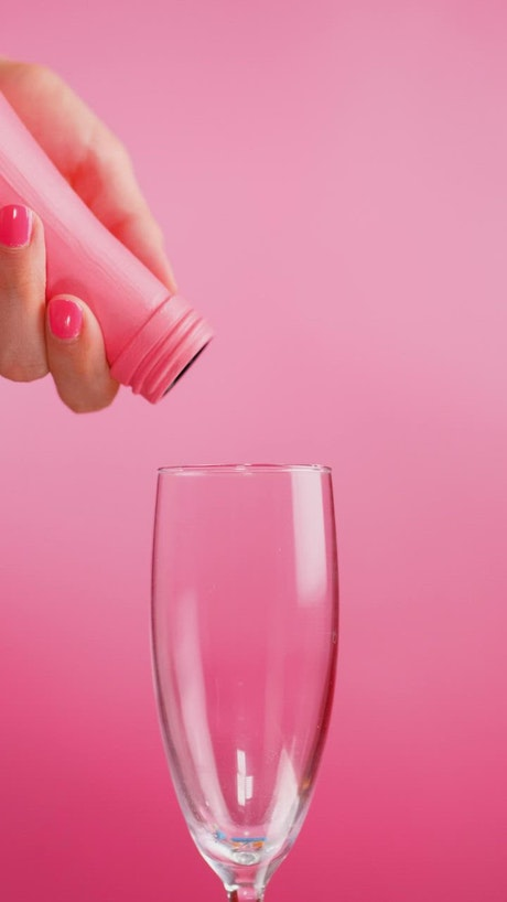 Filling a glass cup with small sweets on a pink background