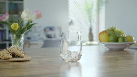 Filling a glass with sparkling water in the kitchen table