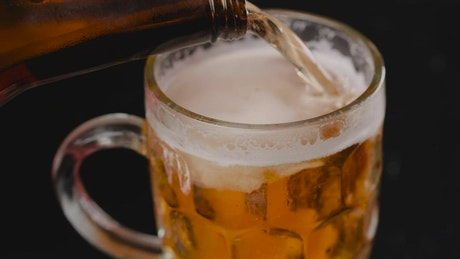 Filling a mug with beer on a dark background