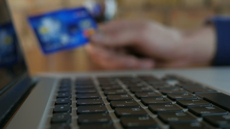Finger typing and unfocused hand holding credit card