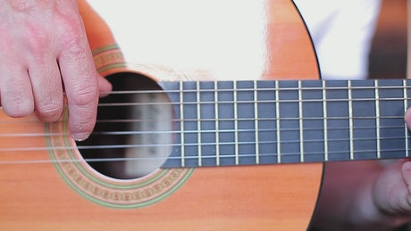 Fingers of a man playing the strings of a guitar