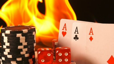 Fire burning behind poker cards, dice and casino chips