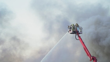 Firefighters on a crane putting out a fire