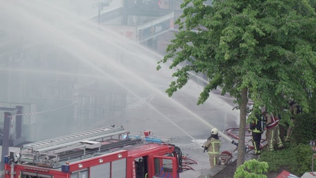 Firefighters on the street shooting water with their hoses