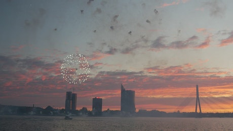 Fireworks above the city in the sunset