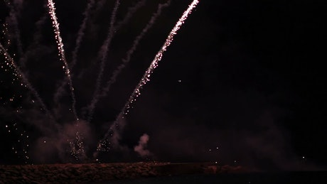 Fireworks rising from a pier