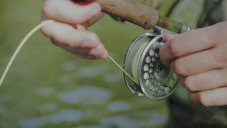 Fisherman rolling the line spool